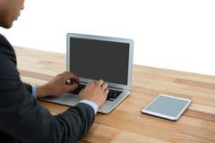 Взгляд со стороны бизнесмена используя портативный компьютер Стоковые Изображения RF