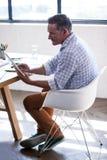 Взгляд со стороны бизнесмена используя планшет Стоковая Фотография RF