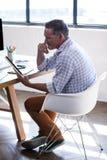 Взгляд со стороны бизнесмена отражая и используя планшет Стоковое фото RF