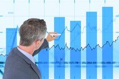 Взгляд со стороны бизнесмена работая на диаграммах Стоковое Изображение