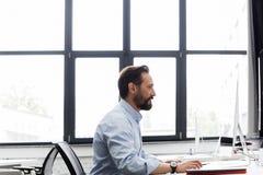 Взгляд со стороны бизнесмена работая на компьютере Стоковое Изображение
