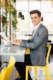 Взгляд со стороны бизнесмена сидя таблицей с портативным компьютером и смотря камеру Стоковое Изображение