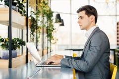 Взгляд со стороны бизнесмена сидя таблицей с портативным компьютером Стоковое Фото