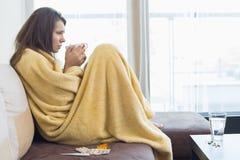 Взгляд со стороны больной женщины имея кофе на софе в живущей комнате Стоковые Фотографии RF