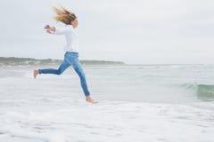 Взгляд со стороны вскользь женщины скача на пляж Стоковое Фото