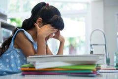 Взгляд со стороны вымотанной девушки сидя книгами в кухне Стоковая Фотография