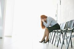 Взгляд со стороны вымотанной коммерсантки сидя на стуле в офисе Стоковые Фотографии RF