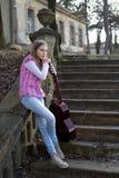 Взгляд со стороны девочка-подростка с склонностью гитары на стене Стоковые Фотографии RF