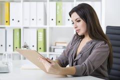 Взгляд со стороны девушки в сером сочинительстве в офисе Стоковые Фото