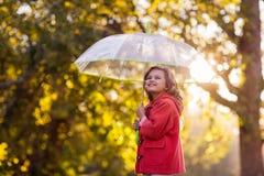 Взгляд со стороны девушки держа зонтик против деревьев Стоковое фото RF