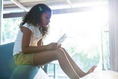 Взгляд со стороны девушки используя таблетку пока сидящ на кресле Стоковые Изображения