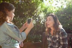 Взгляд со стороны девушки фотографируя мать вставляя вне язык Стоковое фото RF