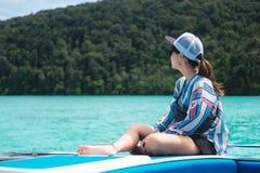 Взгляд со стороны женщина Азии сидя самостоятельно на prow и смотря пейзаж Стоковая Фотография RF