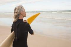 Взгляд со стороны женщины держа surfboard пока стоящ на береге Стоковое фото RF