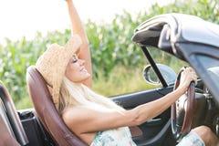 Взгляд со стороны женщины наслаждаясь ездой в автомобиле с откидным верхом outdoors Стоковая Фотография