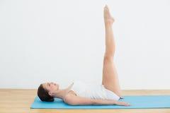 Взгляд со стороны женщины протягивая ноги на циновке тренировки Стоковое Фото