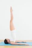 Взгляд со стороны женщины протягивая ноги на циновке тренировки Стоковые Изображения