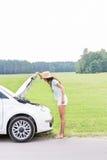 Взгляд со стороны женщины рассматривая сломанный вниз с автомобиля на проселочной дороге Стоковое Изображение