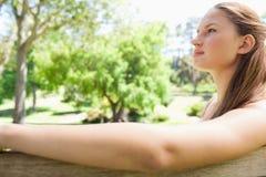 Взгляд со стороны женщины сидя на скамейке в парке Стоковое Фото