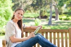 Взгляд со стороны женщины с компьютером таблетки на скамейке в парке Стоковое фото RF