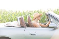 Взгляд со стороны женщины управляя автомобилем с откидным верхом на солнечный день Стоковые Изображения RF