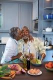 Взгляд со стороны женщины целуя человека пока подготавливающ еду Стоковая Фотография