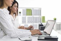 Взгляд со стороны 2 женщин в белом офисе работая совместно Стоковое Изображение RF