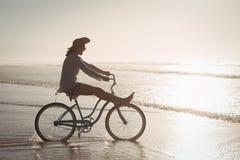 Взгляд со стороны жизнерадостного велосипеда катания женщины на береге на пляже Стоковая Фотография RF