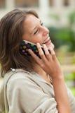 Взгляд со стороны жизнерадостной женщины используя мобильный телефон Стоковое Фото