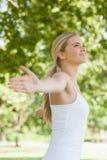 Взгляд со стороны жизнерадостной привлекательной женщины делая йогу распространяя ее оружия Стоковая Фотография