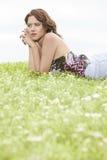 Взгляд со стороны заботливой молодой женщины лежа на траве против ясного неба Стоковая Фотография