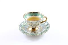 Взгляд со стороны зеленых и белых чашка и поддонника с чаем стоковые фотографии rf