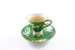 Взгляд со стороны зеленых и белых чашка и поддонника с чаем стоковое фото rf