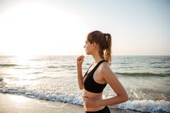 Взгляд со стороны здоровой молодой женщины бежать на пляже Стоковая Фотография