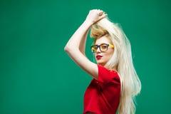 Взгляд со стороны изумляя блондинкы при длинные волосы и Eyeglasses представляя на зеленой предпосылке в студии Стоковые Фото