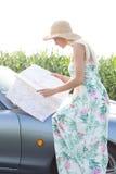Взгляд со стороны карты чтения женщины пока сидящ на автомобиле с откидным верхом Стоковые Фотографии RF