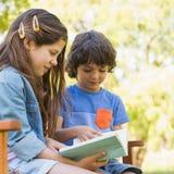 Взгляд со стороны книги чтения детей на скамейке в парке Стоковое Фото