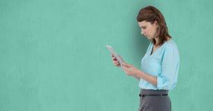 Взгляд со стороны коммерсантки используя планшет над зеленой предпосылкой Стоковые Фотографии RF