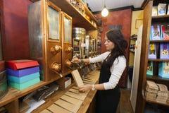 Взгляд со стороны кофейных зерен продавца распределяя в бумажную сумку на магазине Стоковые Фото