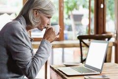 Взгляд со стороны кофе старшей женщины выпивая пока использующ портативный компьютер Стоковые Фотографии RF