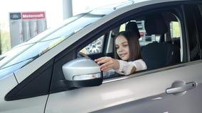 Взгляд со стороны красивого ребёнка смотря отсутствующий и усмехаясь пока сидящ в новом автомобиле в мотор-шоу акции видеоматериалы
