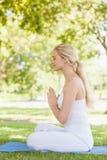 Взгляд со стороны красивой спокойной женщины размышляя сидеть на циновке тренировки Стоковое Изображение RF