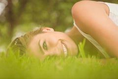 Взгляд со стороны красивой счастливой женщины лежа на траве Стоковое фото RF