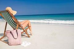 Взгляд со стороны милого брюнет ослабляя на шезлонге на пляже Стоковая Фотография RF