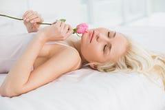 Взгляд со стороны милой женщины в кровати с поднял Стоковое Изображение