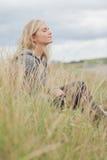 Взгляд со стороны милой заботливой женщины сидя на пляже Стоковое Изображение RF