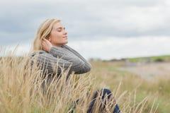 Взгляд со стороны милой заботливой женщины сидя на пляже Стоковые Фотографии RF