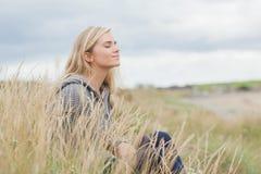 Взгляд со стороны милой заботливой женщины сидя на пляже Стоковые Изображения RF