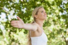 Взгляд со стороны милой молодой женщины делая йогу распространяя ее оружия Стоковые Изображения