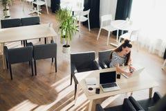 Взгляд со стороны Молодая бизнес-леди сидя на таблице и принимая примечания в тетради На таблице компьтер-книжка, smartphone и ча Стоковые Фотографии RF